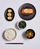 A Japanese meal with dashi broth, salmon, omelette, spinach and rice
