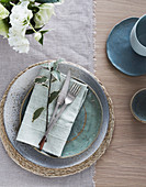 Place setting on linen tablecloth with cloth napkin and sprig of mint