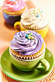 Cupcakes decorated with different coloured buttercream served in colourful tea cups