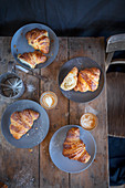 Croissants with cappuccinos on a rustic wooden table (top view)