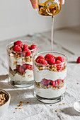 Granola with greek yougurt, raspberries and honey in a glass