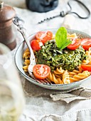 Vegan green pesto with dried tomatoes, seved with gluten-free red lentil fussili pasta