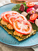 Homemade gluten free seed cracker with vegan pesto, tofu and tomatoes, served with side salad