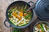 Hühnersuppe mit Nudeln und Gemüse im Gusseisentopf