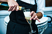 A waiter pouring champagne into a glass
