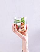 Hand hält Glas mit Nudelsalat