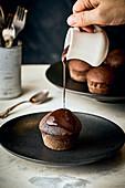 Muffin mit Schokoladensauce begießen