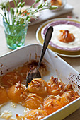 Baked apricots with almonds in a baking dish, served with vanilla ice cream
