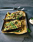 Baked eggplant halves with couscous filling and a tahini dip