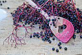 A still life with elderberries and a coloured wooden spoon