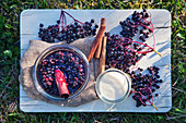 Elderberry compote and ingredients on a wooden board
