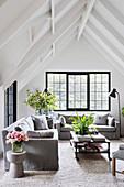 Heller Wohnraum unter weißem Giebeldach mit grauen Sofas und schwarzen Sprossenfenstern