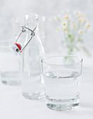 Wasserglas und Bügelflasche mit Wasser