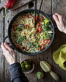 Green curry pasta with limes, herbs and chili pepper in pot on wooden background