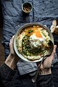 Hände halten eine Schüssel Blumenkohlpüree mit Pesto und pochiertem Ei