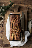 Healthy banana bread in container on chopping board on wooden background