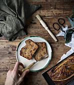 Healthy banana bread in container and slices in a plate on wooden background