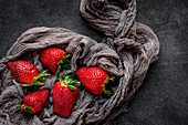 Red and fresh strawberries flat lay in a piece of cloth