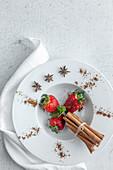 Frische Erdbeeren mit Zimt und Sternanis auf Teller