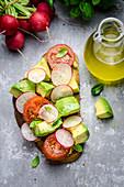 Brot belegt mit Avocado, Tomate und Radieschen