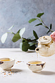Pouring from teapot hot green tea in two traditional chinese clay ceramic cup