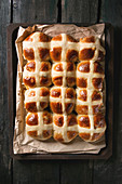 Homemade Easter traditional hot cross buns on oven tray with baking paper over dark wooden background