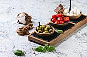 Mozzarella, Kirschtomaten und Oliven als Antipasti in Holzschälchen