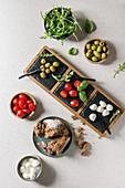 Antipasti mit Mozzarella, Kirschtomaten, Oliven, Brot und Rucola