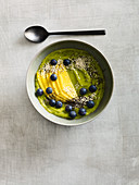 A green smoothie bowl with chia, avocado and blueberries