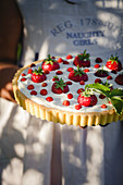 Mascarpone tart garnished with garden and wild strawberries