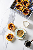 Puff pastry tarts filled with pudding, served with coffee