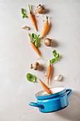 Möhren, Pilze, Basilikum und Knoblauch fallen in einen Topf