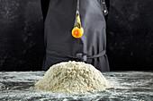 A broken egg falling in a heap of flour