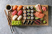 Sushi Set: nigiri, sashimi and sushi rolls on wooden serving board with soy sauce and chopsticks
