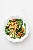 Spinach salad with peppers, zucchini and fried chickpeas