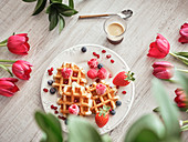 Dish with delicious waffles and fresh berries between red tulips on board