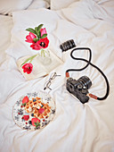 Dish with delicious waffles and fresh berries on bed with camera, book and phone