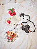 Waffeln mit frischen Beeren auf Bett mit Fotoapparat, Buch und Brille