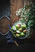 Teller mit grün-roten Birnen auf Holztisch mit Blumen