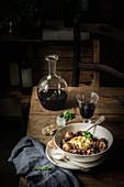 Boeuf Bourguignon und Rotwein auf rustikalem Holztisch