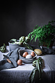 Eggs and different herbs in bowls placed on rustic table
