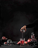 Hand pouring pomegranate juice from bottle to glass on black background