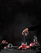 Granatapfelsaft aus Flasche in Glas giessen