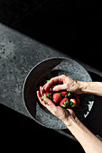 Hands holding pile of fresh strawberry near bowl illuminated by sunbeams in darkness