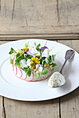 Potato salad spread with sour cream and edible flowers