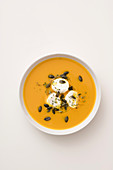 Cream of pumpkin soup with rosemary, goat's cheese and pumpkin seeds