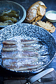 Raw soused herring with sea salt, bread and gherkins