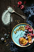 A vegan blue smoothie bowl with spirulina, fruits and nuts