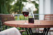 A glass of red wine and a carafe of wine on a wooden table in a garden