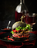 A black burger with mushrooms, peppers and salad